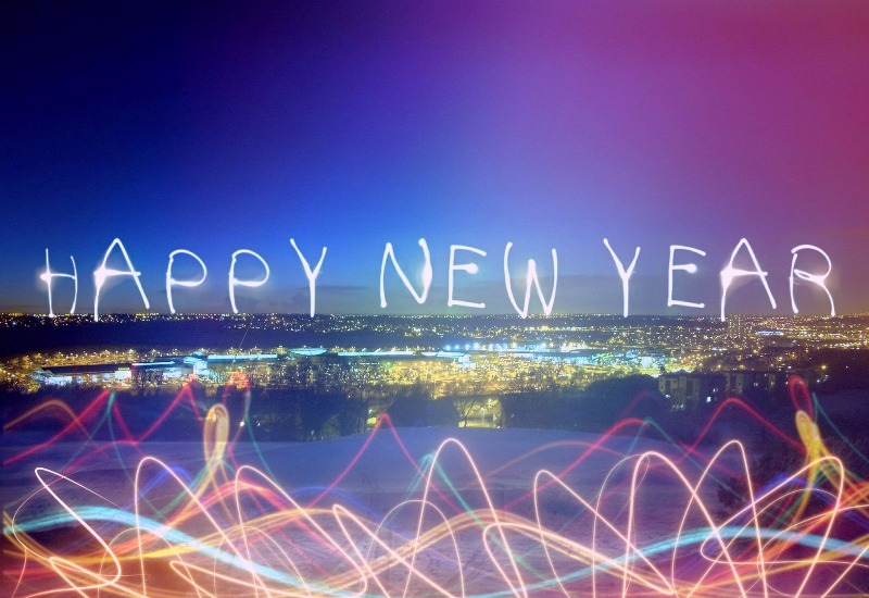 "Landscape photo of a city skyline lit up at light with firework lights spelling out ""Happy New Year"""