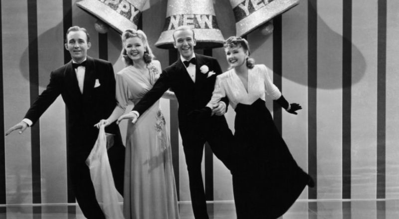 Screen capture of the cast from Holiday Inn (Bing Crosby, Marjorie Reynolds, Fred Astaire, and Virginia Dale) posed in front of a New Year's Eve stage background.