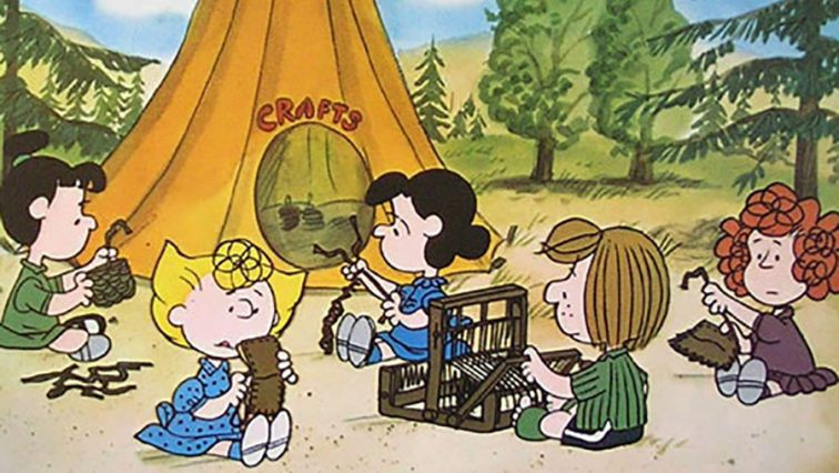"Peanuts characters, Sally, Peppermint Patty, and Lucy, knitting outside of a camping tent that reads ""Crafts"" on the outside."