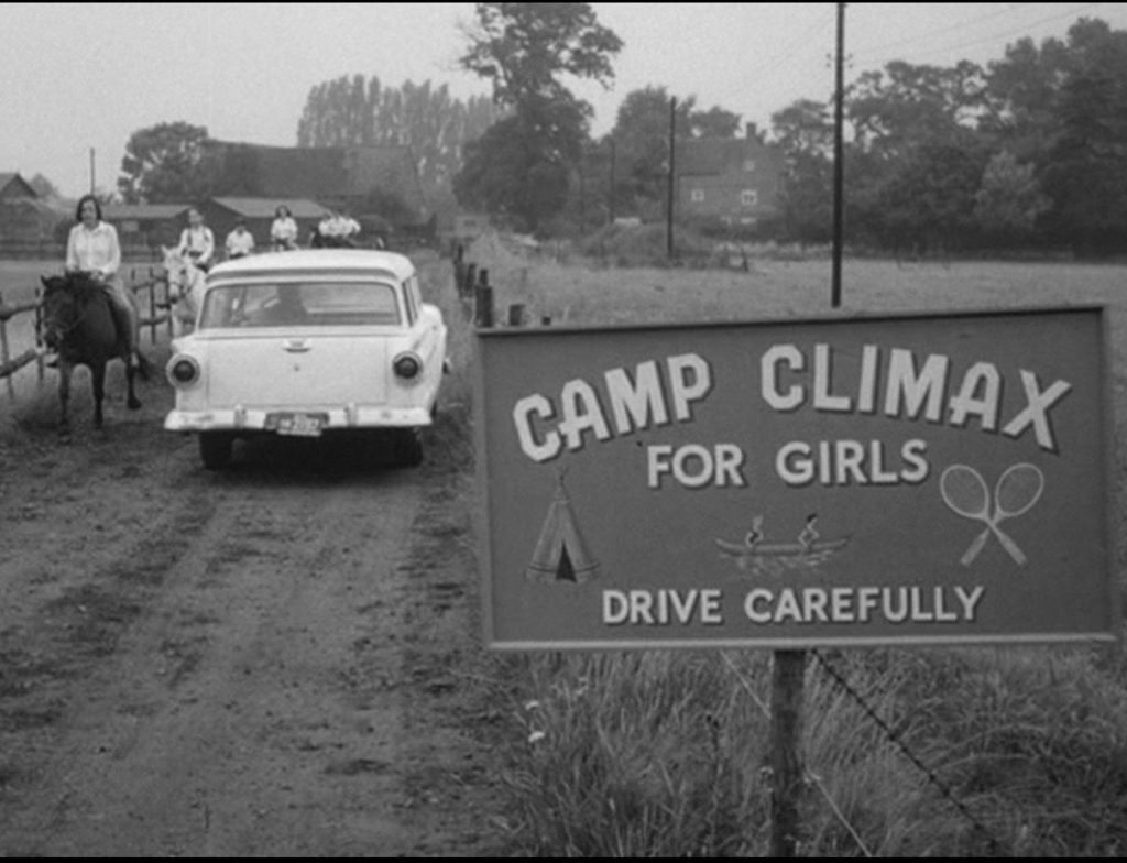 "A black and white still from the 1962 film Lolita, a large white station wagon drives past a wooden sign that reads ""Camp Climax for girls"""