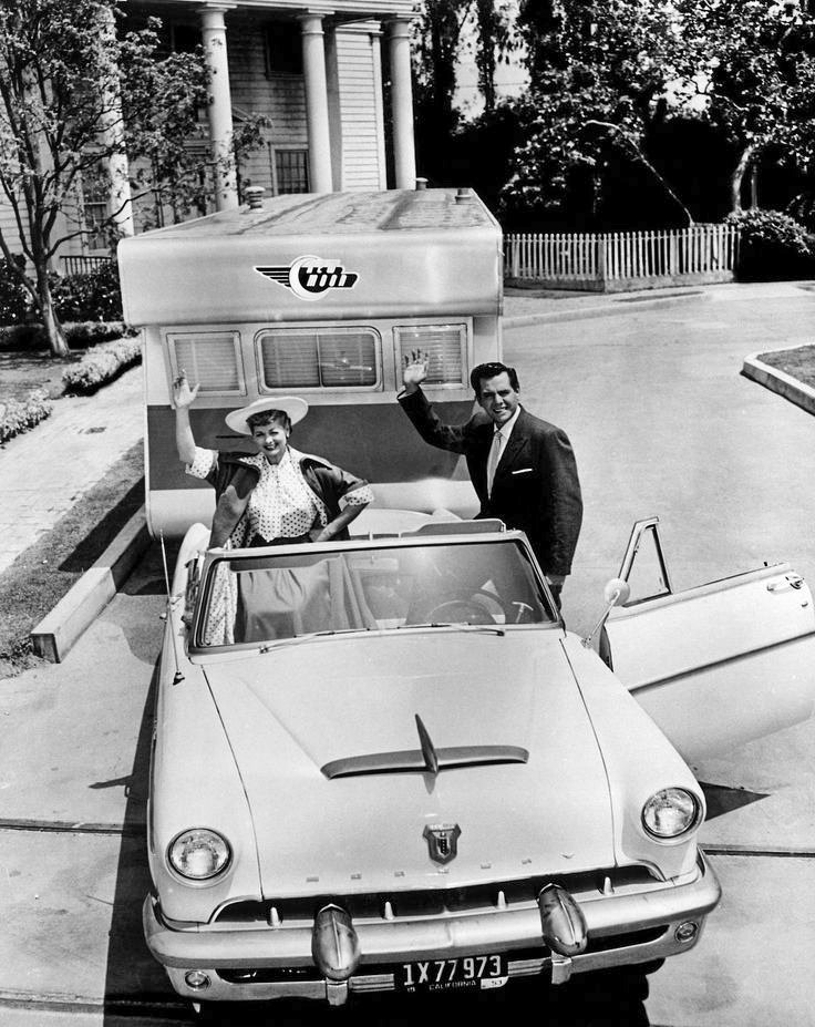 Still from the 1954 trailer The Long Long Trailer with Desi Arnaz and Lucille Ball waving at the camera from the front seats of a 1950s convertible, pulling a trailer behind it.
