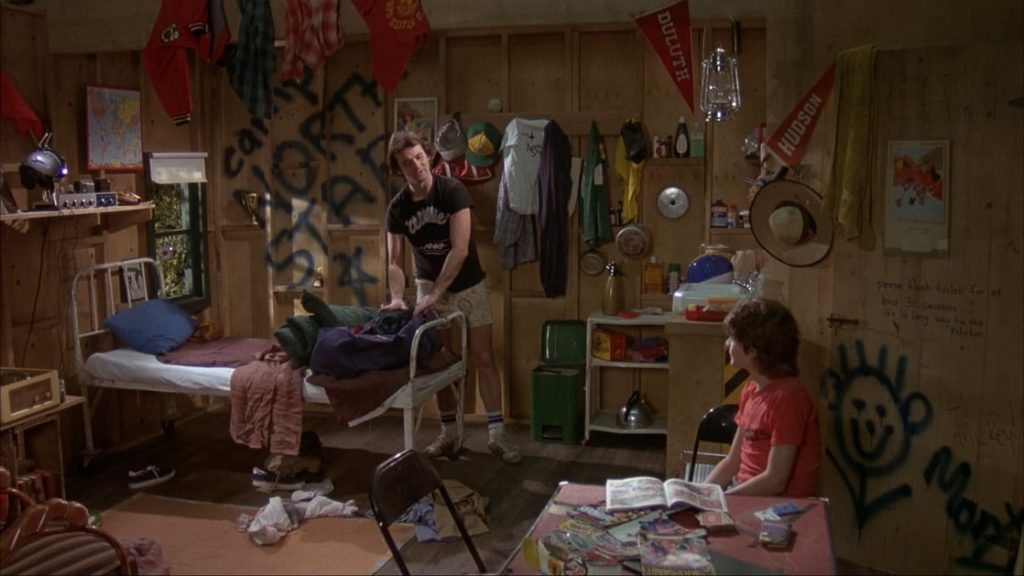 A still from the 1979 Meatballs, Bill Murray perches in a messy counselors room, talking with a camper.