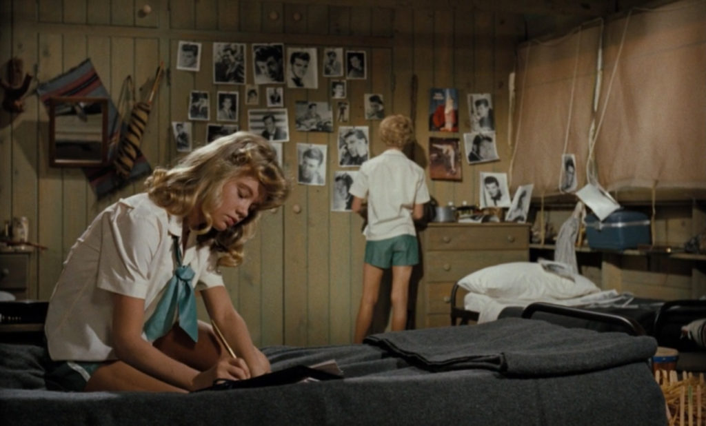 Still from the 1961 film The Parent Trap. Two pre-teen girls, both played by Hayley Mills, are busy writing letters & hanging pictures in their cabin.
