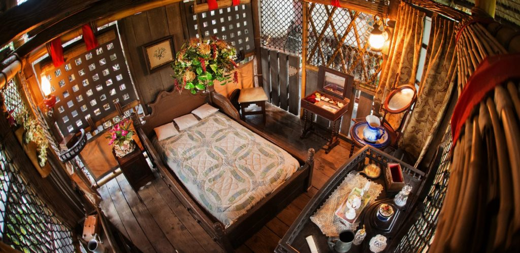A bedroom from the Swiss Family Robinson treehouse located in Walt Disney World a blend of old world European finery, a bed, a lamp, a silver kettle, and rustic furniture crafted from tropic woods.