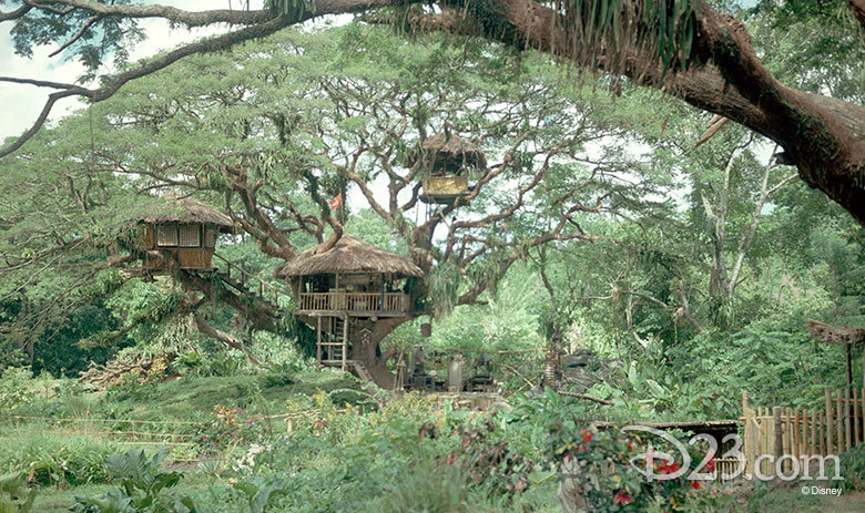 A still from the 1960 film The Swiss Family Robinson, with verdant green tropical jungle and a multi-level tree house build of bamboo and palms among the branches.