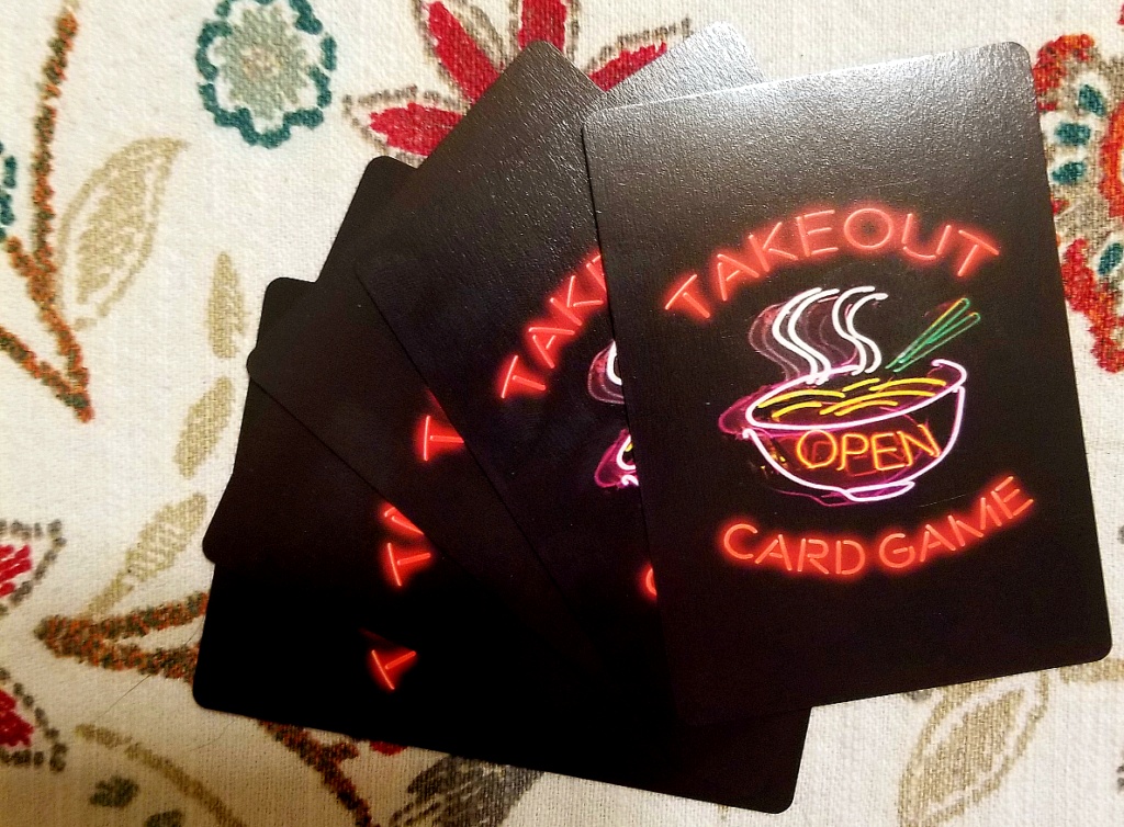 "A fan of five cards, showing a black background and a design of a neon sign of a noddle bowl with chopsticks and ""Takeout Card Game"""