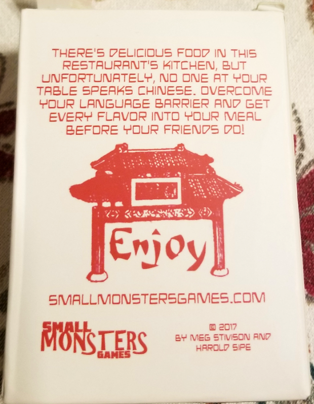 "Back of the deck box for Takeout, showing an arch with the word ""Enjoy"" and the description, ""There's delicious food in this restaurant's kitchen, but unfortuantely, no one at your table speaks Chinese. Overcome your language barrier and get every flavor into your meal before your friends do!"""
