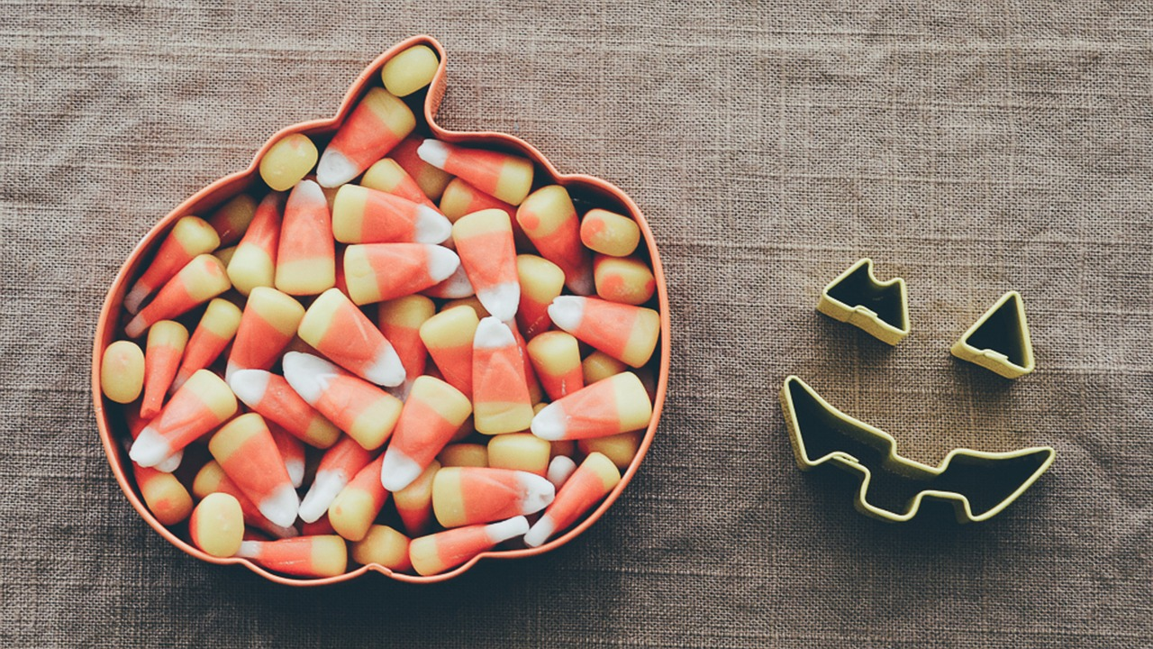 Candy corn filling a pumpkin shaped cookie cutter. To the right are cookie cutter shapes for a jack'o'lantern mouth and eyes.