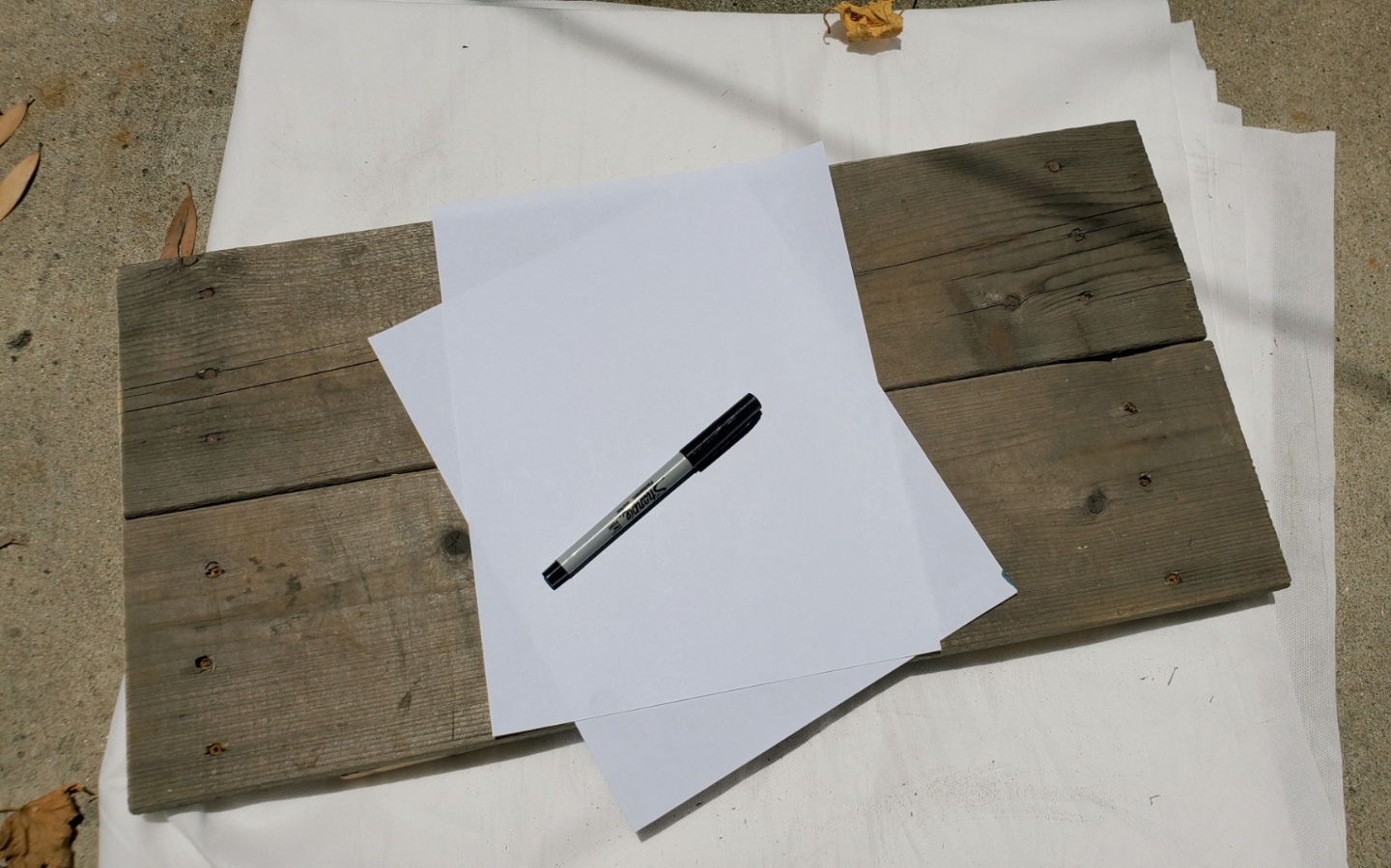 Two pieces of paper and a marker sitting on the wood surface