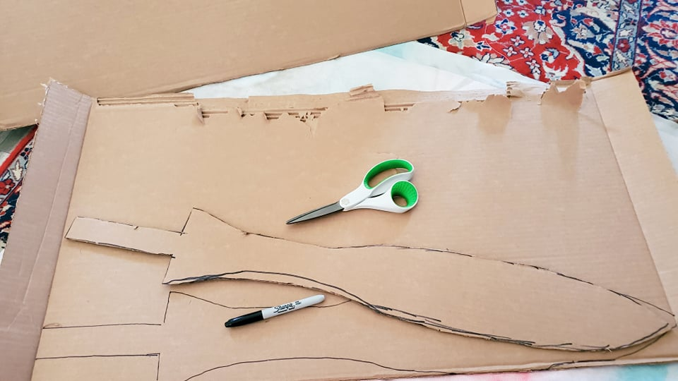 a sword shape traced out twice onto a large piece of cardboard and cut so that it makes mirrored pieces