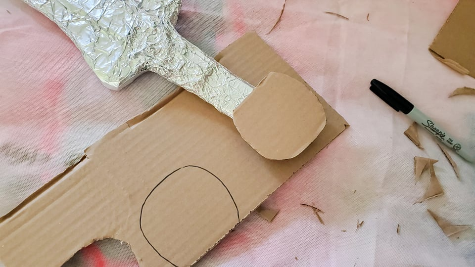 2 round pieces of cardboard cut to be the pommel on each side of the sword hilt