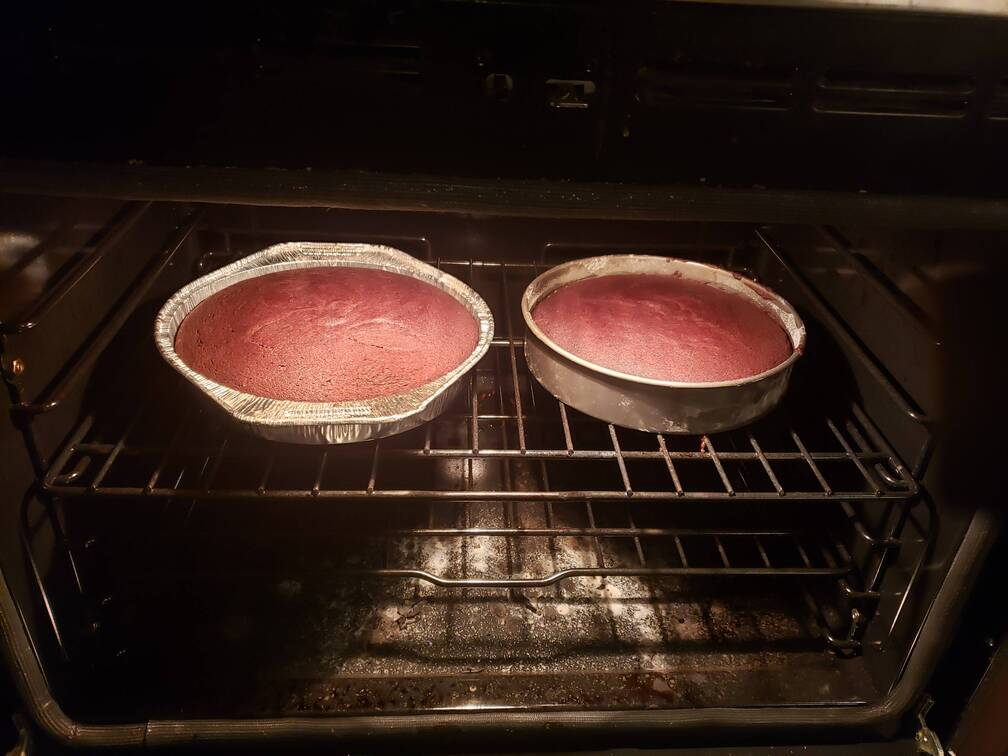 2 cake pans with reddish brown cake, baking in the oven