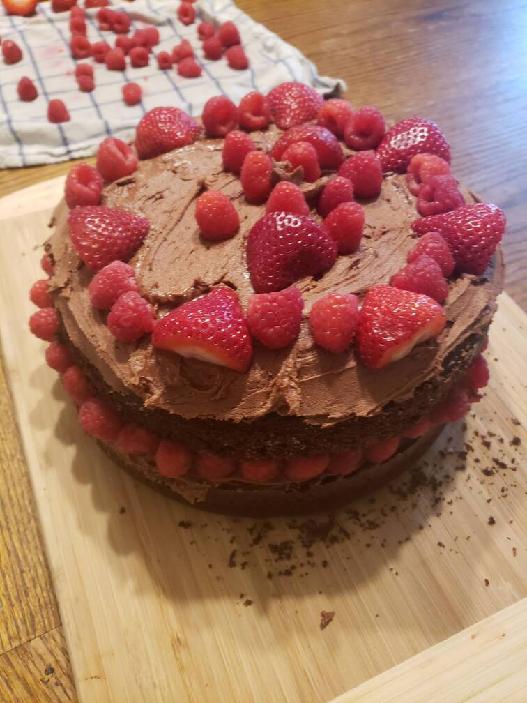 finished cake with chocolate frosting and fresh raspberries for toppings