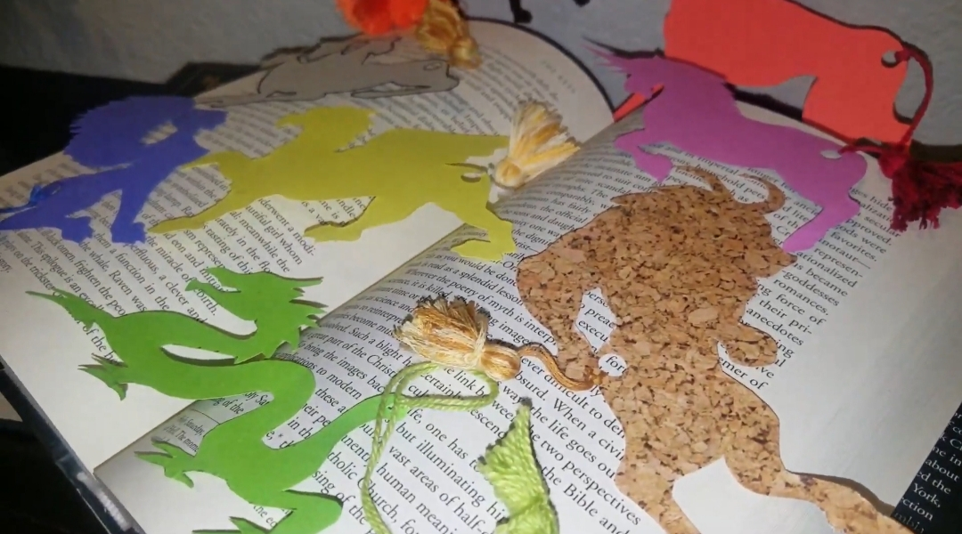 A variety of paper-cut outs of mythical creatures with string tails are scattered atop an open book