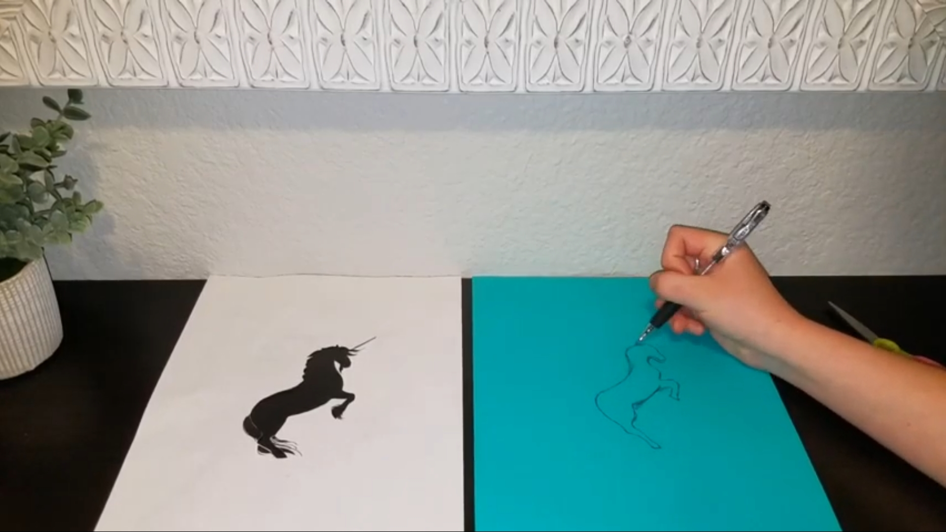 A silhouette of a unicorn on the left with a hand using a pencil to copy the outline freehanded on the right