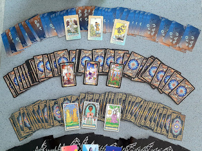 A spread of tarot decks laid out in a fan across a table