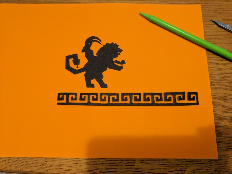 """geometric pattern in black cardstock pasted below the """"chimera"""" silhouette on the orange card stock"""