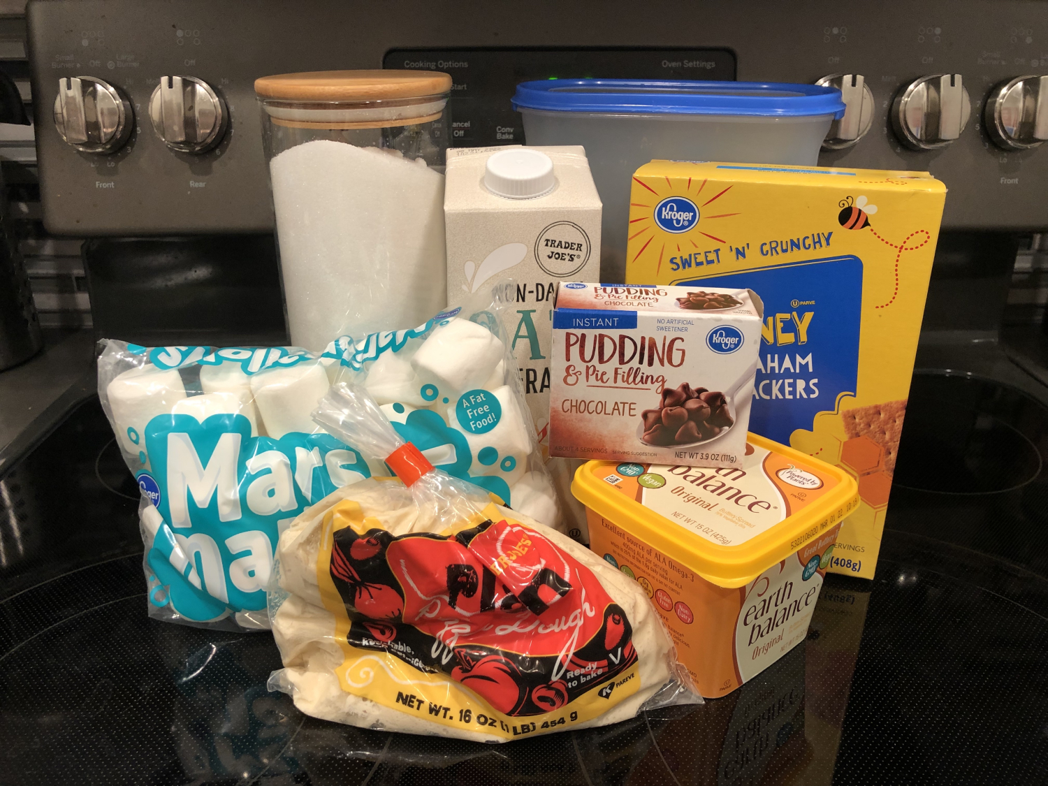 All of the ingredients for smores pizza including graham crackers, marshmallows, milk, butter, chocolate chips