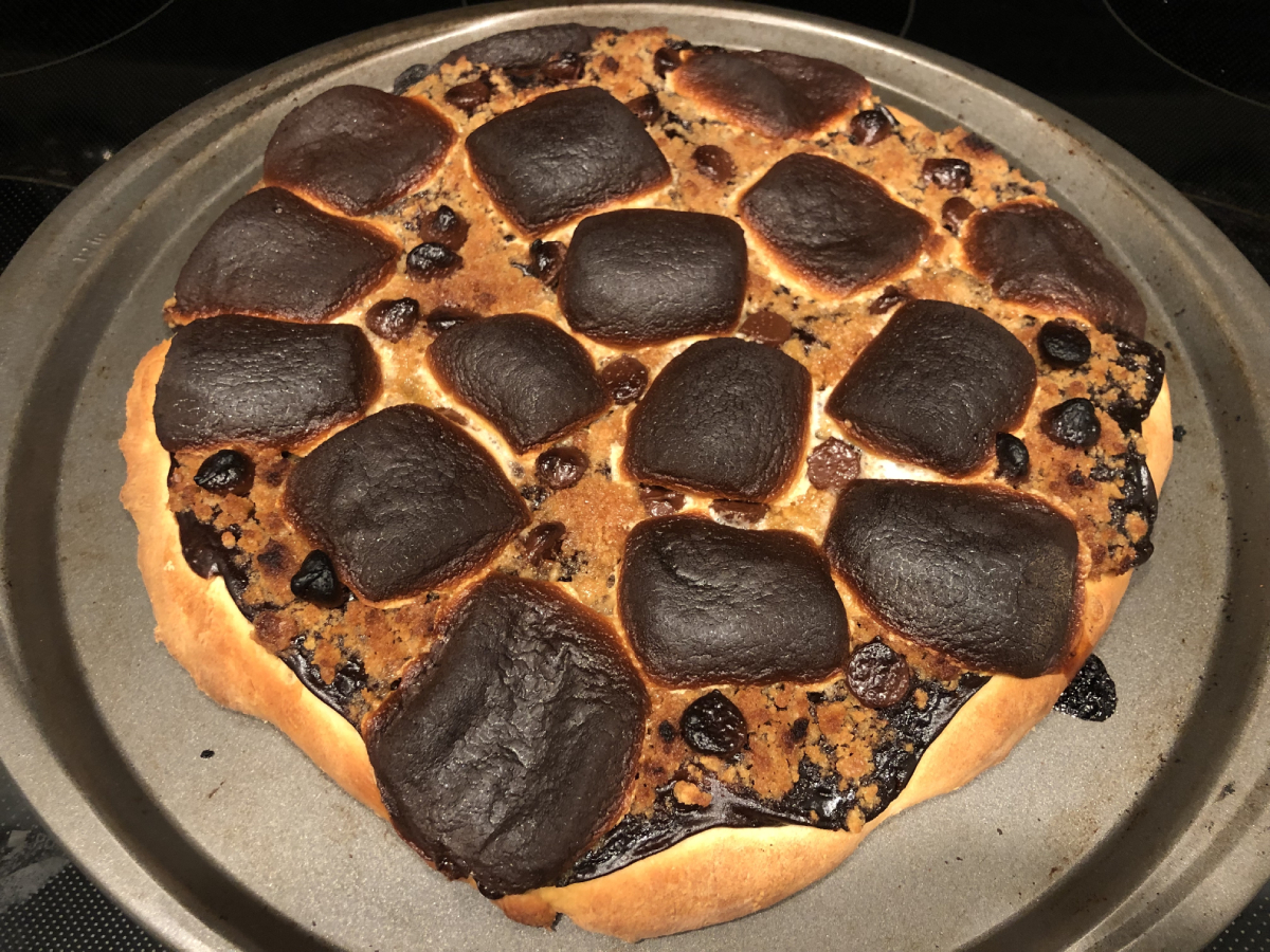 Baked s'mores pizza; graham has turned golden brown and marshmallows have a crispy outer coating