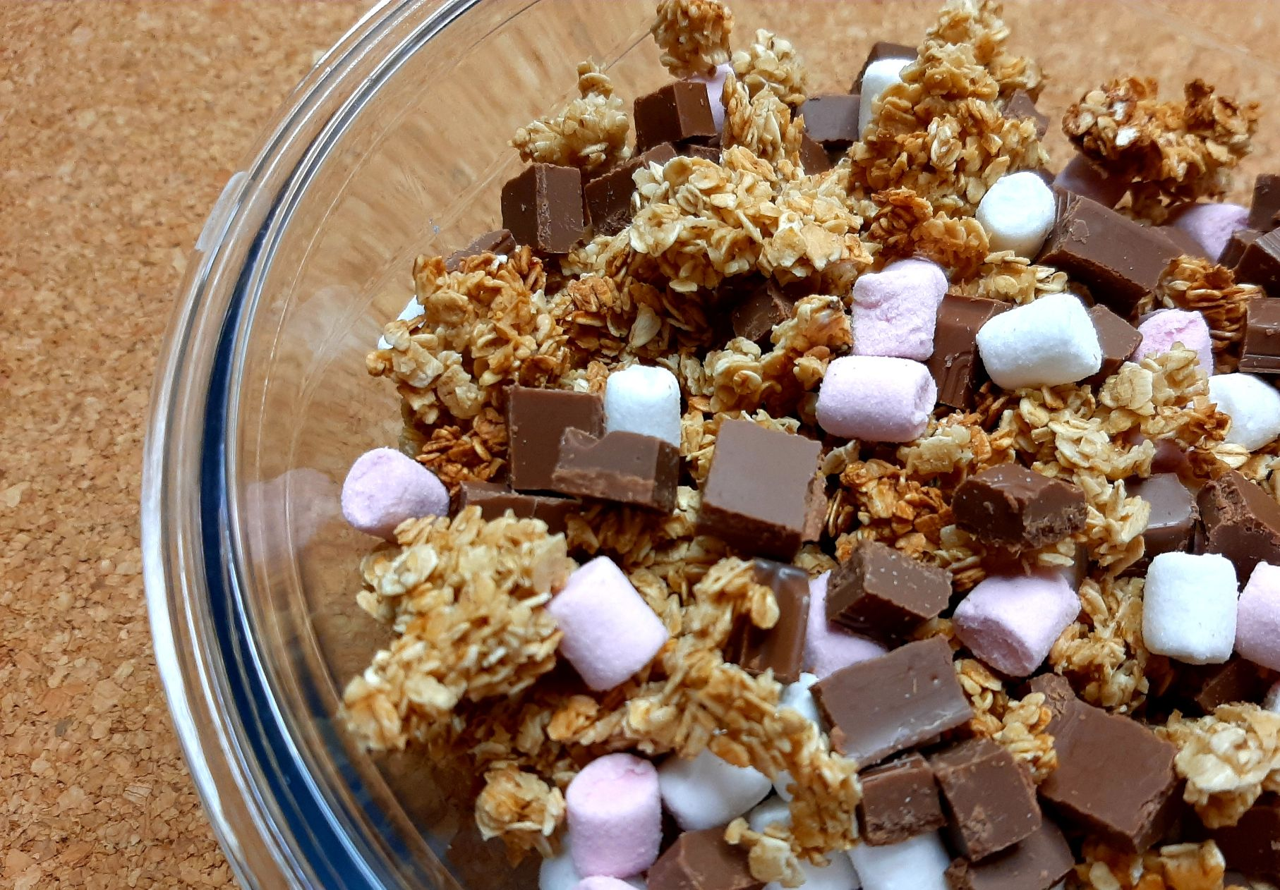 large granola pieces with chocolate chunks and mini marshmallows, in a glass bowl on a wooden surface