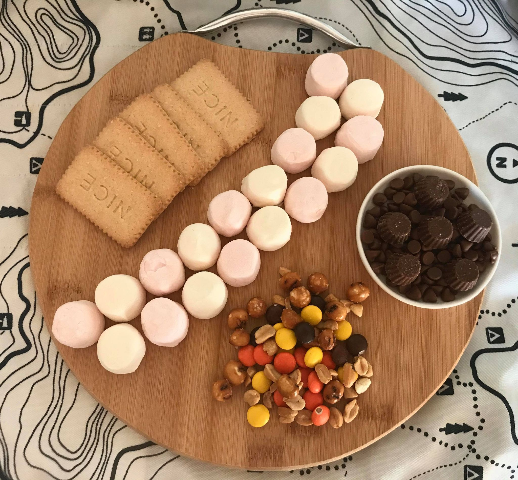 a round wooden board with biscuits, marshmallows, small candies, and chocolate dipping sauce arranged on it